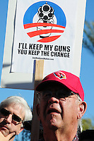 """Phoenix, Arizona. January 19, 2013 - """"I'll keep my guns, you keep the change,"""" reads this sign seen during Saturday's pro-guns rally in Phoenix. As President Barack Obama proposed new gun regulations last week, gun owners demonstrated against it with national """"Guns Across America"""" rallies to defend the Second Amendment. Dozens showed up at the Arizona State Capitol, many of them carrying weapons. Photo by Eduardo Barraza © 2013"""