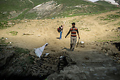 A cleaner hired by local authorities throws the a bag of collected garbage back into the river along the Amarnath trekking route in Kashmir, India. Hindu pilgrims brave sub zero temperature and high latitude passes and make their pilgrimage to reach the sacred Amarnath cave, which houses a lingam - a stylized phallus, worshiped by Hindus as a symbol of God Shiva. Photo: Sanjit Das/Panos