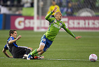 Seattle Sounders FC midfielder Osvaldo Alonso is tripped by San Jose Earthquakes midfielder Sam Cronin during play between the Seattle Sounders FC and the San Jose Earthquakes at CenturyLink Field in Seattle Saturday October 15, 2011. The Sounders FC won the game 2-1.