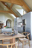Behind the cook's island is a wall of b3 cabinetry which is finished in glossy natural aluminium and was custom-made by Bulthaup to fit beneath the roof beams