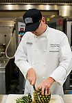 Jeffrey Arthur, the new culinary services executive chef for Ohio University, cuts a pineapple preparing for the day.