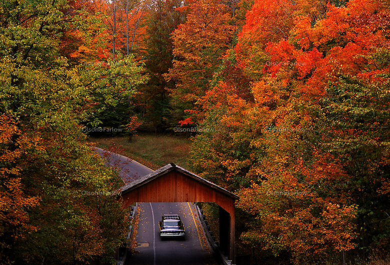 Cars pass through a covered bridge on Pierce Stocking Scenic Drive in Sleeping Bear Dune National Lakeshore in the northwest section of Michigan's lower peninsula.  The seven and a half mile drive passes through forest, across dunes and provides views of Glen Lake, Sleeping Bear (the shape of a dune that park was named for) and Lake Michigan.