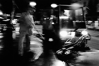 Switzerland. Geneva. Garbage collectors. Streets cleaning.  A street sweeper with his broom, another worker driving a street brooming machine, both are cleaning the street in the early morning.  Night time. © 1991 Didier Ruef