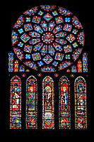 Medieval Rose Window of the North Transept of the Gothic Cathedral of Chartres, France- Circa 1235. A UNESCO World Heritage Site. The 10.5m rose window is dedicated to the Virgin Mary . The central oculus shows the Virgin and Child and is surrounded by 12 small petal-shaped windows, 4 with doves (the 'Four Gifts of the Spirit'), the rest with adoring angels carrying candlesticks. Beyond this is a ring of 12 diamond-shaped openings containing the Old Testament Kings of Judah, another ring of smaller lozenges containing the arms of France and Castille, and finally a ring of semicircles containing Old Testament Prophets holding scrolls. The presence of the arms of the French king (yellow fleurs-de-lis on a blue background) and of his mother, Blanche of Castile (yellow castles on a red background) are taken as a sign of royal patronage for this window. Beneath the rose itself are five tall lancet windows (7.5 m high) showing, in the centre, the Virgin as an infant held by her mother, St Anne - the same subject as the trumeau in the portal beneath it. Flanking this lancet are four more containing Old Testament figures. Each of these standing figures is shown symbolically triumphing over an enemy depicted in the base of the lancet beneath them - David over Saul, Aaron over Pharaoh, St Anne over Synagoga, etc