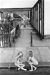 Elephant and Castle, London. 1975<br /> In just their under clothes on a fine summers day two small girls chat sitting on the pavement in front of their post-Second World War prefabs homes.