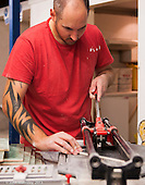 Trainee tiler using the tile cutter,  Able Skills training centre, Dartford, Kent.