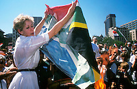 A white woman burns the new South African flag at a right-wing demonstration in Pretoria. It became the official flag of South Africa in April 1994 to represent the move from apartheid to multiracial democracy.