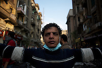 A young egyptian protestor helps form a human shield to prevent the advance of the security forces during violent clashes in central Cairo.