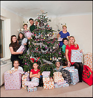BNPS.co.uk (01202 558833)<br /> Pic: PhilYeomans/BNPS<br /> <br /> Think your Xmas is hectic??<br /> <br /> Rayna Warriner(39) from Bournemouth in Dorset has nine children to contend with every festive season, and even such simple tasks as getting the tree ready takes a military style operation.<br /> <br /> Present buying starts in the January sales, wrapping is a 3 day operation Xmas dinner is for 12...but at least the tree only takes a minute to dress, with 9 willing helpers.<br /> <br /> And both Stress manager Rayna and Police officer husband Malcolm manage to hold down full time jobs after packing the kids off to school every day.<br /> <br /> Rayna organises children (Clockwise from Raina) Avie(6), Ilish(8), Callan(11), Meredith(8) Taitum(10), Jackson(14), Eryn(16), Romany(8), Harrison(13).
