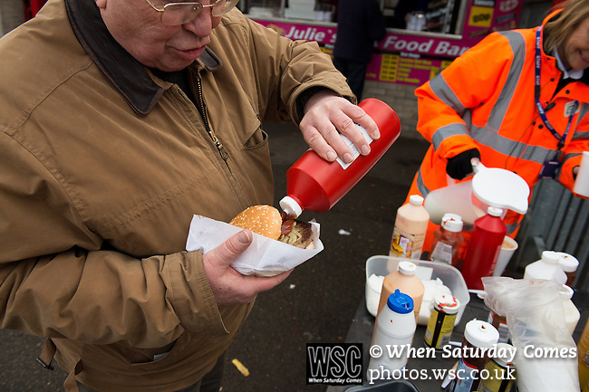 Dagenham and Redbridge 1 Burton Albion 3, 21/02/2015. Victoria Road, League Two. A Dagenham supporter enjoys a pre match burger. Burton Albion moved to the top of League Two following a hard-fought win over Dagenham & Redbridge played in-front of 1,718 supporters. Photo by Simon Gill.