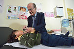 Dr. Husein Mady examines a Syrian refugee child in a clinic in Kamd El Loz, in Lebanon's Bekaa Valley. Run by the Amel Association, the clinic's work with refugees is supported by International Orthodox Christian Charities, a member of the ACT Alliance. Note that the poster on the left of the back wall may violate the International Code of Marketing of Breast-milk Substitutes....