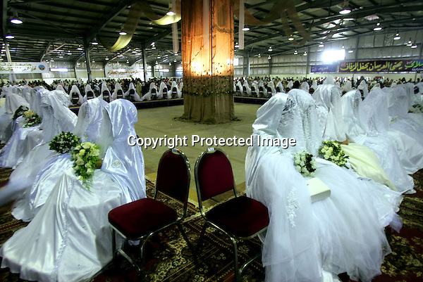 AMMAN, JORDAN- JULY 30: Jordanian brides stay to celebrate with their female relatives and friends as their grooms left to the side where males are celebrating a mass wedding for needy people in Amman July 30, 2004. One hundred and fourty six brides and grooms got married on Friday in a celebration with their families made by the Moslem Brothers . (Photo by Salah Malkawi)