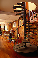 A metal spiral staircase creates a sculptural feature in this loft space with brick walls and a wooden floor