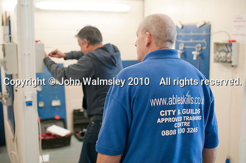 Student electrician watched by an instructor, Able Skills, Dartford, Kent.