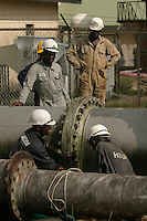 Shell operations in Niger Delta. Bonny oil terminal where oil is exported. Workers dismanteling old oil pipe line. © Fredrik Naumann