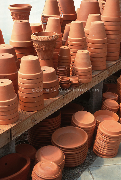 Pots & containers in piles on potting shed bench, new clean unused terracotta clay pots ready for planting