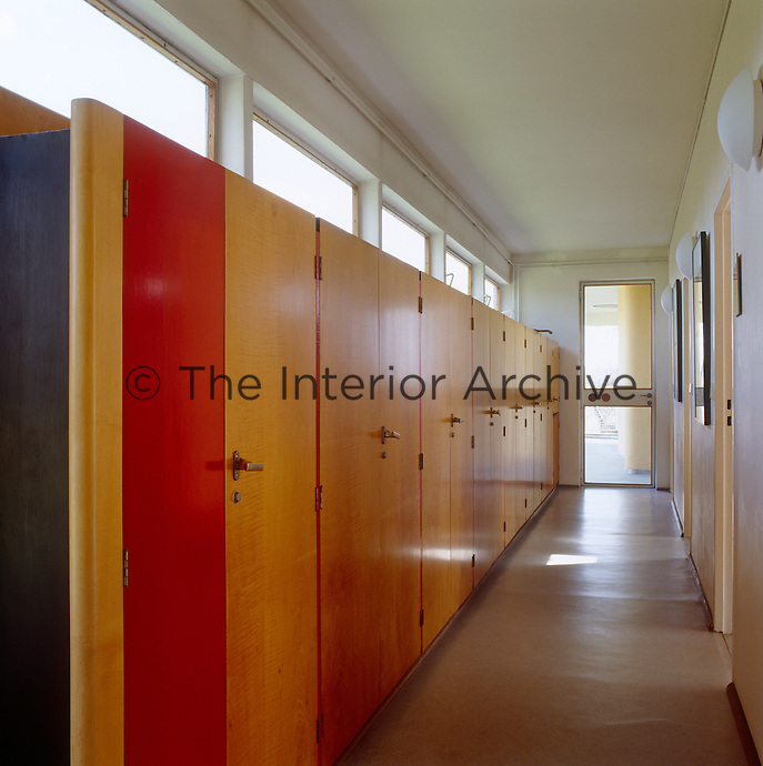 An enfilade of built-in cupboards in natural varnished plywood line the corridor outside the children's bedrooms