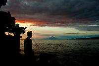 A Balinese man in traditional dress and headgear gazes toward Gunung Agung, Bali's sacred mountain.