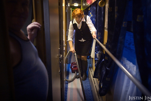 A Russian conductor cleans a train that travels across Russia. The train, beginning in Berlin, Germany, goes through Poland and Belarus, and ends in Irkutsk, Russia. The entire journey takes six days.