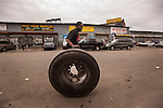 QUEENS, NY -- OCTOBER 22, 2013:  Jason Velaquez, 25, rolls a truck wheel through Willets Point on October 22, 2013 in Queens.  Photographer: Michael Nagle for The New York Times