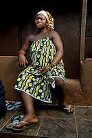 Kroo Bay, Freetown, Sierra Leone...Story on child and maternal health in the Kroo Bay slum community in Freetown, Sierra Leone, which has the World's worst infant and maternal mortalitly rates. One in 4 children die before they reach the age of 5 and one in 6 mothers dies during child birth (in the UK, the rate is one in 3,800)...The Kroo Bay Community Health Centre has a catchment area of over 8,000 people but lacks adequate facilites to provide even basic care. The clinic lacks even the basics, such as bedpans, surgical spirits and cotton wool. It has no electricity and clean drinking water must be fetched from the nearby well everyday...Aminata Kamara (28) outside her home. Aminata is nine months pregnant and due to deliver any day...© 2007 Aubrey Wade. All rights reserved.