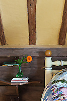 A detail in the bedroom shows the wall planking under the sloping ceiling with an ingenious built-in bedside table