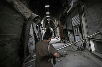 A Syrian opposition fighter is seen running at one section of the souk of the Old City damaged by heavy shelling beside the Umayyad Mosque in the northern Syrian city of Aleppo.