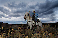 Under stormy evening skies, Edgar Oscanoa rides Dot trailing sheep in Upper Gully .<br /> .Sharon O'Toole drove her granddaughter Siobhan Lolly and father George Salisbury around the Ladder Livestock Ranch in southern Wyoming (west of Bags at the Colorado border.) Peruvian shepherds traditionally work at the ranch watching over sheep.  Dot, an adopted mustang that came from the correctional center in Riverside, saved a shepherd's life by finding his way home on a cold night when they were lost.  Nelson, the saved worker, left years ago but the horse is still a favorite among ranch hands like Edgar. He is steady--rock solid--as they guard the sheep.