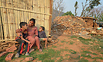 With her sons Sandesh, 10, and Safal, 5, Maya Thapalyia sits in front of her family's transitional shelter with the ruins of her former house in the background. She and her family live in Majhitar, Nepal. Their home was damaged in an April 2015 earthquake that ravaged the region, but Dan Church Aid, a member of the ACT Alliance, has helped the indigenous community to rebuild, including providing Thapalyia's family with their transitional home.