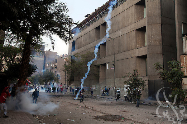 Egyptian protestors take cover as a tear gas canister fired by nearby security forces lands in their midst during street battles November 21, 2011 near Tahrir square  in central Cairo, Egypt. Thousands of protestors demanding the military cede power to a civilian government authority clashed with Egyptian security forces for a third straight day in Cairo, with hundreds injured and at least 24 protestors killed.  (Photo by Scott Nelson)
