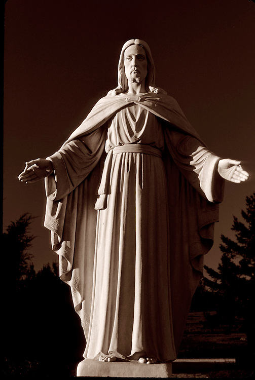 Cemetery statue of Jesus in full sun at midday with rich shadows, Toronto, Ontario.