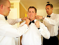 Groom Chris gets help getting ready from his groomsmen before his wedding in Napa, California.