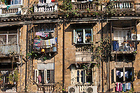 Tenement block traditional chawl housing scheme with air conditioning units and man in window in Parel area of Mumbai, India