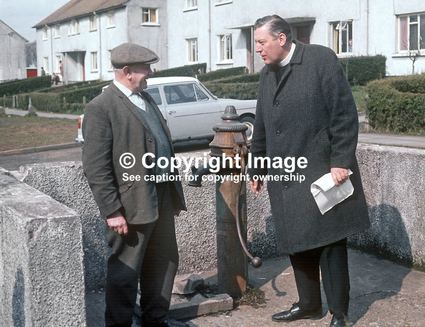 Rev Ian Paisley canvassing as the Protestant Unionist candidate in the Bannside, Co Antrim, constituency by-election of 16th April 1970 caused by the resignation of Terence O'Neill, the sitting MP. He had resigned the previous year as N Ireland's Prime Minister being succeeded by Major James Chichester-Clark. Rev Ian Paisley literally engages in parish pump politics with Cullybackey resident, James Baird, who complained about the absence of running water in the Queen's Park houses 17 years after they were built. 197004000113e<br />