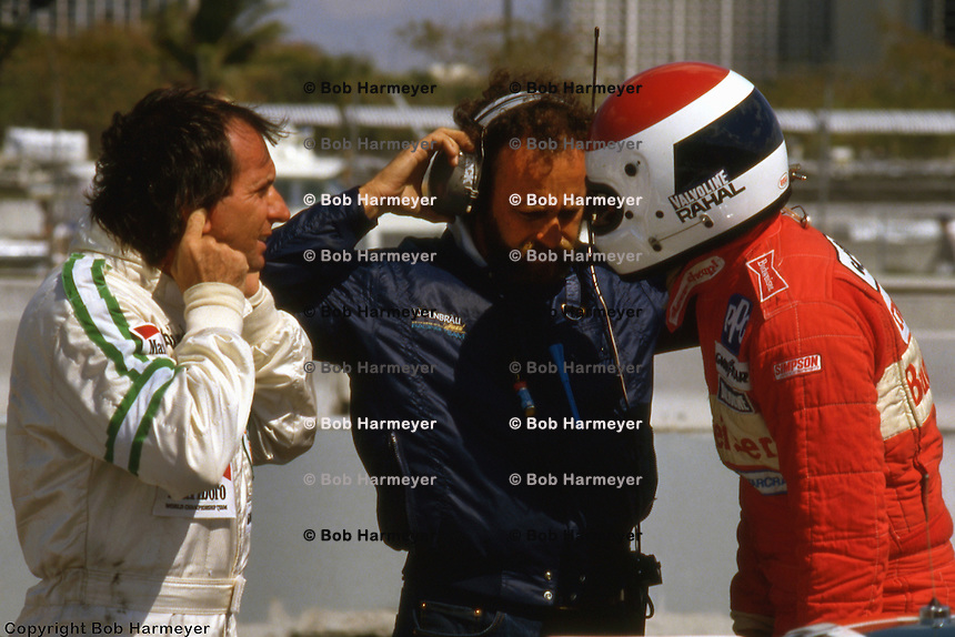 MIAMI, FL - MARCH 2: Teammates Emerson Fittipaldi (left) and Bobby Rahal (right) confer in the pit lane during practice for the Lowenbrau Grand Prix of Miami on March 2, 1986, on the temporary street circuit in Bicentennial Park in Miami, Florida.