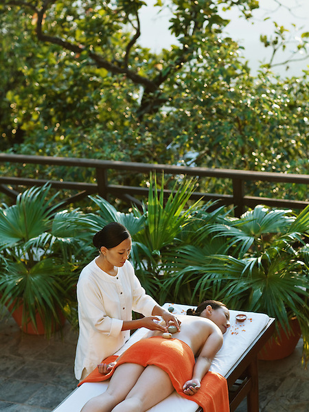 Woman Receiving Tibetan Massage at Sunset, Ananda Spa, Ananda in the Himalayas, The Palace Estate, Narendra Nagar, Tehri Garhwal, Uttarakhand, India. The stones used in the Tibetan Massage symbolize the 5 elements: SA or earth, CHU or water, ME or fire, LUNG or air, and NAMKHA or sky.