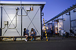 As dusk falls two elementary school children can be seen playing cards in a temporary housing estate established for those who lost their homes during the March 11 quake and tsunami in Natori City, Miyagi Prefecture Prefecture, Japan on 08 Sept. 2011.  Photograph: Robert Gilhooly