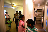 Mohamud Ali, 48, from Somalia, with his wife Fadumo, 36, and five children at the house that Mohamud has just purchased for 200 thousand $.As he says, it was worth twice as much last year. Mohamud is showing his family their new home, happy that he could buy it so cheap..This area has been badly hit by crisis in property market. Lots of houses are foreclosed or abandoned. Value of many properties here has dropped by half within one year.   .Manassas Park, Northern Virginia, USA .June 2008.<br /> <br /> (Photo by Piotr Malecki / Napo Images)  <br /> Somalijczycy Mohamud Ali i jego rodzina, ktorzy kupili za pol ceny jeden z domow przejetych przez bank poznaja swoje nowe miejsce.Polnocna Wirginia, a szczegolnie Prince William County jest jednym z najmocniej dotknietych kryzysem nieruchomosci miejscem w Stanach Zjednoczonych. Setki tysiecy domow sa opuszczane przez wlascicieli bez widokow ani na ich sprzedaz ani na splate zaciagnietego kredytu.Woodbridge, Wirginia, USA Czerwiec 2008.<br /> (Photo by Piotr Malecki / Napo Images)