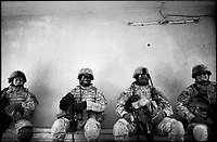 U.S. soldiers relax as they wait for an improvised explosive device (IED) which was found in their patrol area, to be defused in Baghdad August 12, 2007.