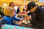 Dec. 12, 2012 - Garden City, New York, U.S. - At left, BARBARA MEYER, of Woodbury, wraps a gift of jewelry to help the Merrick Kiwanis Club, a community service group, raise funds to use for charity, during the busy winter holiday shopping season at Roosevelt Field mall in Long Island. She was one of several members of Meadowbrook Women's Initiative who helped out at the booth. Some ways Kiwanis helps the community are by providing food, clothing, and school supplies to those in need, sending children to Kamp Kiwanis, providing scholarships and hosting a Harvest Ball for senior citizens.