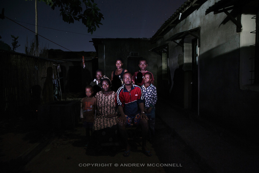 Congolese refugees, the Mwanmba family: (L-R) Didier, Leonardo, Bambi Byumbay Florence, 35, Marie Clementine, Didier Mwamba, Jean Kevin, and Eddy Joyeux, pictured at their home in Bujumbura, Burundi.<br /> <br /> Words of Bambi Byumbay Florence<br /> In 1996 there had been many rumours saying that people were coming from the outside to attack Congo. I remember it was raining, there were rumours that at the 7 in the evening we were told people would come form Mariba. Then a few minutes later we heard the attack and these people came. I remember we were in a house with 2 rooms and the toilets were outside. We had to go outside to hide, as it was very dark we saw people going inside the house, they searched but didn't find anything. They started a fire in my sisters room, when they did this my husband wanted to go out thinking that my sister was in that room because at that time she was only 10, he left the toilets to go inside the house, they got him then they asked him &quot;where were you?&quot; he said, &quot;I was only in the toilets&quot;, then they said &quot;we will close our eyes and then we don't want to see you again&quot;. So my husband left. <br /> <br /> When the house was on fire everything got burned, I stayed in the toilets, I spend the night there. Inside the house everything had been burned, even my diploma. We couldn't say who they were but I remember I was told that they were coming from Rwanda and Uganda, I remember we called them black people because they were really really dark. At around 10am young people came with the head of someone on a branch so we were obliged to flee, with this head we were really traumatised. Everywhere we passed there were dead bodies, when we crossed Uvira we headed to Mykibola Kigongo, everyone was heading there and everywhere there were dead bodies. Then we came to a checkpoint, here they would just look in your face and tell you to step aside, or for another person they could say &quot;ok continue&quot; and then for