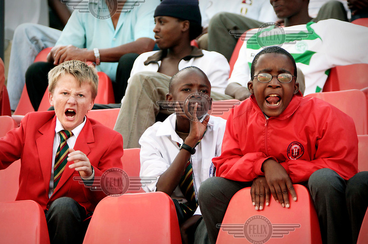 Black and white schoolboy football fans at a Cosmos match at the Rand Stadium.