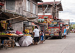 Shoppers check out the produce at market stands on a rainy day in Sampaloc, Quezon Provice, the Philippines.