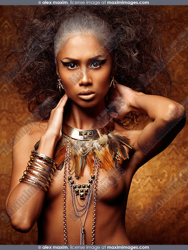 Exotic beauty portrait of a young woman with bird theamed styling, feathery necklace and accessories
