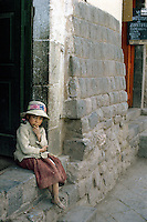 Girl sitting at doorway between Inca walls in Cuzco, Peru