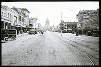 In the picture you can see Congress Avenue as it appeared in 1913, looking toward the capitol building. Horse drawn carriages going up and down Congress Avenue cobblestone streets next to the cable car tracks leading up the Texas State Capitol in downtown Austin, Texas.