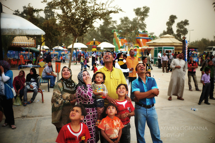 A family watches a new amusement park ride in Baghdad's Zawra Park.