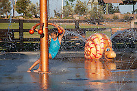 A girls in a blue bathing suit applies all her weight to turn a rotating water feature at the splash pad at Stanton Central Park. The orange metal and her blue suit reflect off of the wet ground, and water can be seen spraying everywhere.