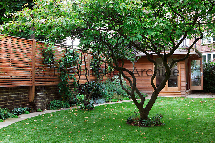 A wooden cabin style summer house in the garden of a town house.
