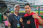 "9 June 2013: Sports photographer Ed Wolfstein (left) is presented with a gift from Washington Nationals Training Assistant John Hsu prior to a game against the Minnesota Twins at Nationals Park in Washington, DC. The Korean writing depicts ""Victory"" which the Nationals accomplished by shutting out the Twins 7-0 in the first game of their Day-Night Double-Header. Mandatory Credit: Ed Wolfstein Photo *** RAW (NEF) Image File Available ***"